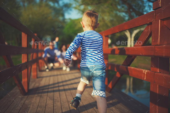 funny boy running on wooden bridge - Stock Photo - Images