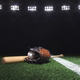 Baseball, mitt and bat on field below lights at night - PhotoDune Item for Sale