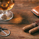 Cuban cigars closeup on wooden desk, blur glass of brandy - PhotoDune Item for Sale