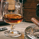 Cuban cigar and a glass of brandy on wooden background, closeup view with details - PhotoDune Item for Sale