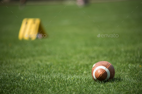 American football ball and green grass field - Stock Photo - Images