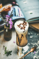 Iced mocha coffee with whipped cream in glass, wooden background