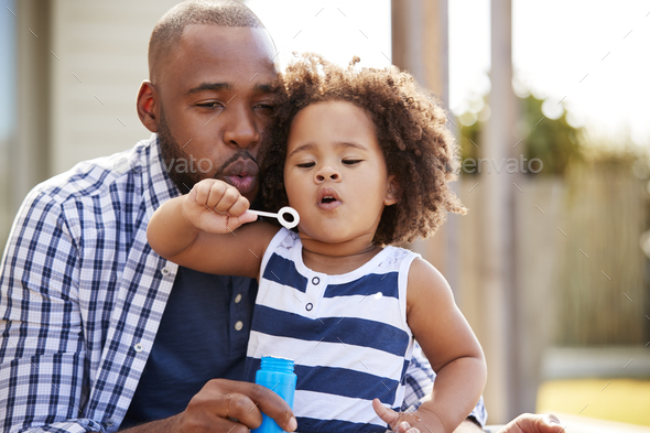Young black father and daughter blowing bubbles outside Stock Photo by monkeybusiness