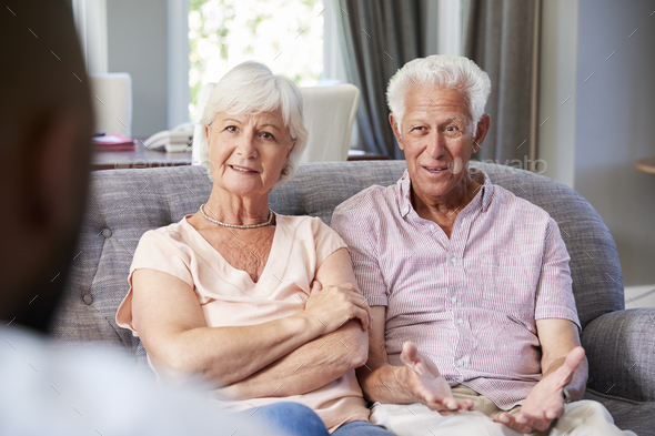 Happy senior couple taking financial advice at home - Stock Photo - Images