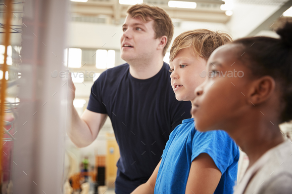 Teacher and kids looking at a science exhibit, close up