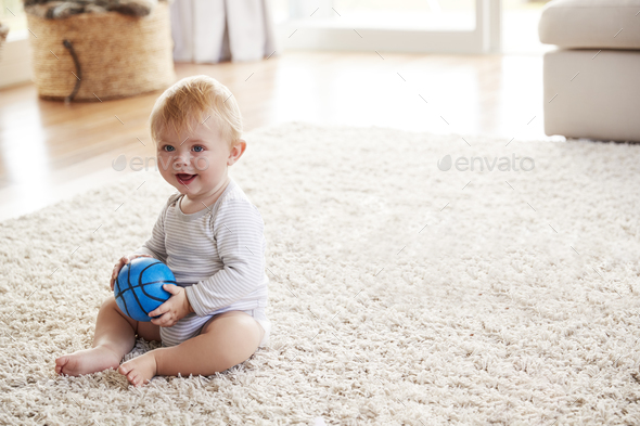 White toddler boy sitting on the floor in sitting room - Stock Photo - Images