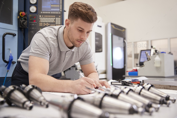 Male Engineer Measuring CAD Drawings In Factory - Stock Photo - Images