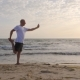 Sports Man Doing Stretching Exercise To Leg on Sea Shore During Morning Workout Using Phone - VideoHive Item for Sale