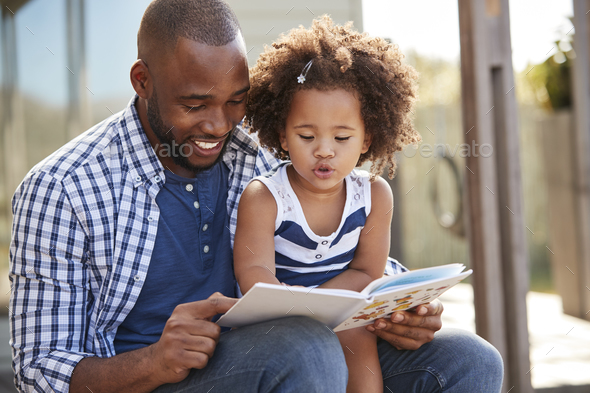 Young black father and daughter reading book outside Stock Photo by monkeybusiness