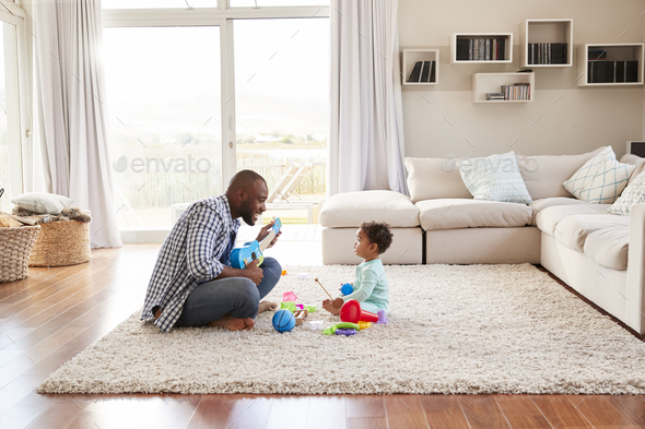Black father and toddler son playing in sitting room Stock Photo by monkeybusiness