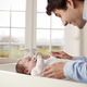 Father Playing With Newborn Baby Lying On Changing Table - PhotoDune Item for Sale