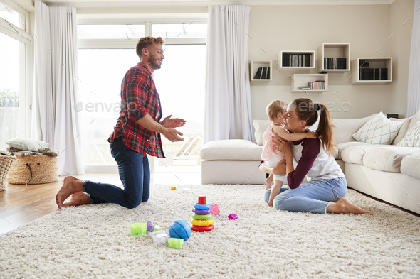 Toddler girl walking from dad to mum in sitting room - Stock Photo - Images
