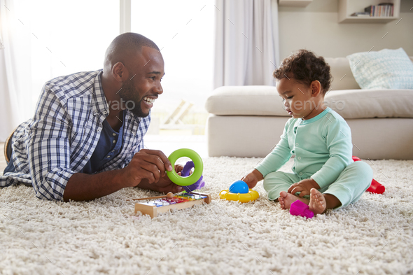 Black dad and toddler son playing on floor at home, close up - Stock Photo - Images