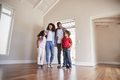 Family Opening Door And Walking In Empty Lounge Of New Home - PhotoDune Item for Sale