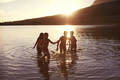Children With Friends Enjoying Evening Swim In Countryside Lake - PhotoDune Item for Sale
