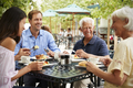 Senior Parents With Adult Children Enjoying Meal At Outdoor Cafe - PhotoDune Item for Sale