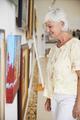 Senior Woman Looking At Paintings In Art Gallery - PhotoDune Item for Sale