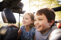 Children Sitting In Back Seat Of Open Top Car On Road Trip - PhotoDune Item for Sale