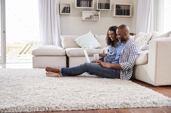 Young black couple sit on the floor using laptop, side view - Stock Photo - Images