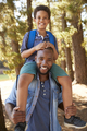 Portrait Of Father Walking In Woods Carrying Son On Shoulders - PhotoDune Item for Sale