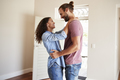 Excited Couple Hugging By Open Front Door In Lounge Of New Home - PhotoDune Item for Sale