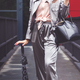 Trendy woman in silver pants jacket with black leather hand bag and umbrella. Fashionable outfit - PhotoDune Item for Sale
