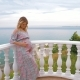 A Pregnant Girl Stands on the Balcony Next To the Sea and Caresses Her Tummy - VideoHive Item for Sale