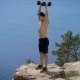 Shot of a Man on a Hill Pushing Dumbbells Up. - VideoHive Item for Sale