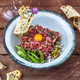 Steak tartare served with raw quail egg yolk and other tartare ingredient. Meat dish. - PhotoDune Item for Sale