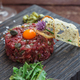 Beef tartare with capers, pickled cucumber and fresh onions on dark background - PhotoDune Item for Sale