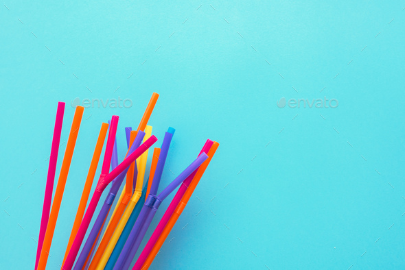 Colorful drinking straws on blue background - Stock Photo - Images