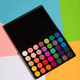 Eyeshadow palette laying on a colorful background. - PhotoDune Item for Sale