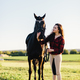 Young woman dressed casually petting black horse - PhotoDune Item for Sale