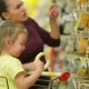 Smiling Mother and Daughter at the Supermarket. A Daughter Helps Her Mother Choose an Adhesive Tape - VideoHive Item for Sale