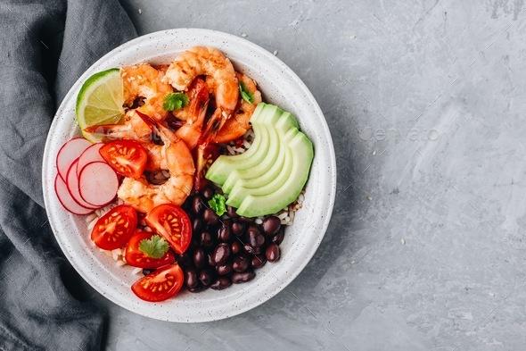 Spicy Shrimp Burrito Buddha Bowl with wild rice, tomatoes and radish, black beans and avocado - Stock Photo - Images