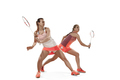 Young women playing badminton over white background