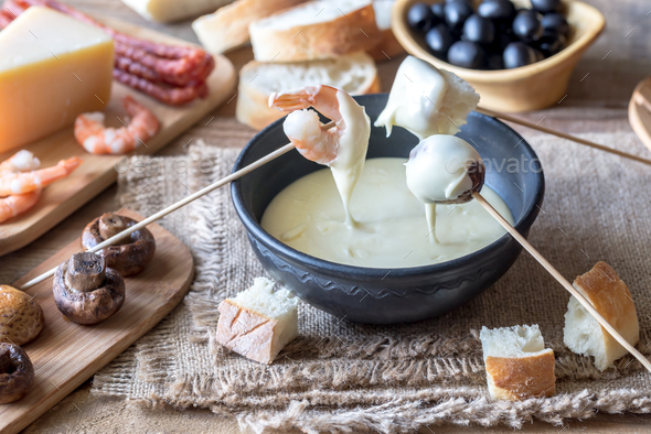 Bowl of fondue with appetizers - Stock Photo - Images