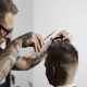 Tattoed Barber Makes Haircut for Customer at the Barber Shop By Using Scissors and Comb - VideoHive Item for Sale