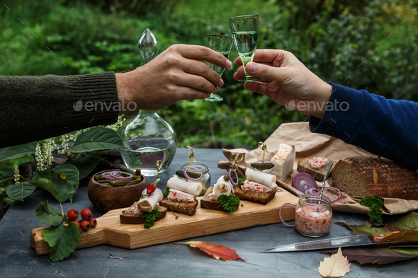 Two hands with shots of vodka, outside dinner - Stock Photo - Images