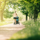 Running woman with baby stroller enjoying summer in park - PhotoDune Item for Sale
