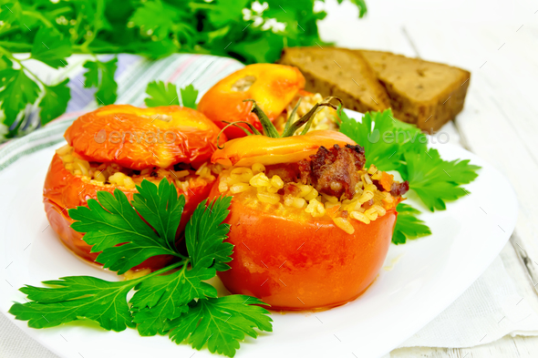Tomatoes stuffed with bulgur and parsley in plate on board - Stock Photo - Images