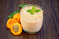 Milkshake apricot in glassful on board