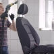 Car Wash Worker Is Cleaning Seat of Automobile in a Room, Using Vacuum Cleaner, Seat Is Standing on - VideoHive Item for Sale