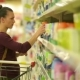 Beautiful Women Chooses Spray. A Supermarket Cart with Products Near Her. - VideoHive Item for Sale