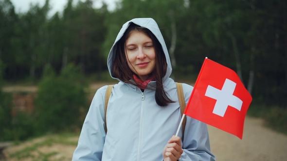 portrait of pretty swiss girl holding flag of switzerland smiling