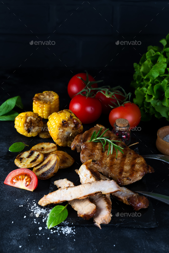 Grilled pork steak and vegetable , baked potatoes and green salad on dark - Stock Photo - Images