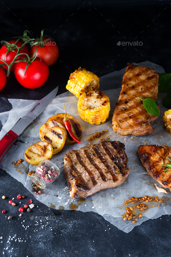 Three types of grilled meats with vegetables and spices on paper - Stock Photo - Images