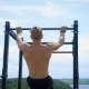 Young Muscular Sportsman Is Lifting His Body Holding Crossbar Outdoors in Summer Day - VideoHive Item for Sale