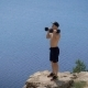 Young Powerlifter Is Lifting Dumbbells By Both Hands Standing on Edge of Cliff Over Sea - VideoHive Item for Sale