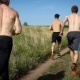 Three Adult Sportsmen with Naked Torso Are Running Over Ground Road in Countryside in Sunny Summer - VideoHive Item for Sale